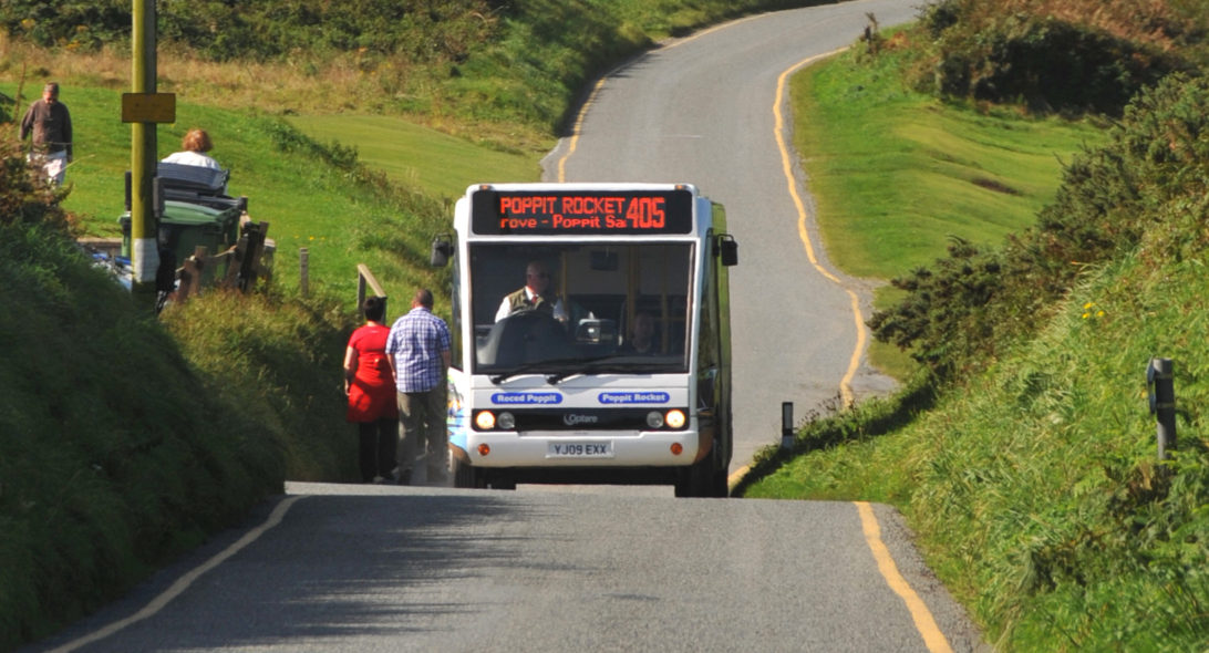 Bus picking up passengers on a narrow coastal road