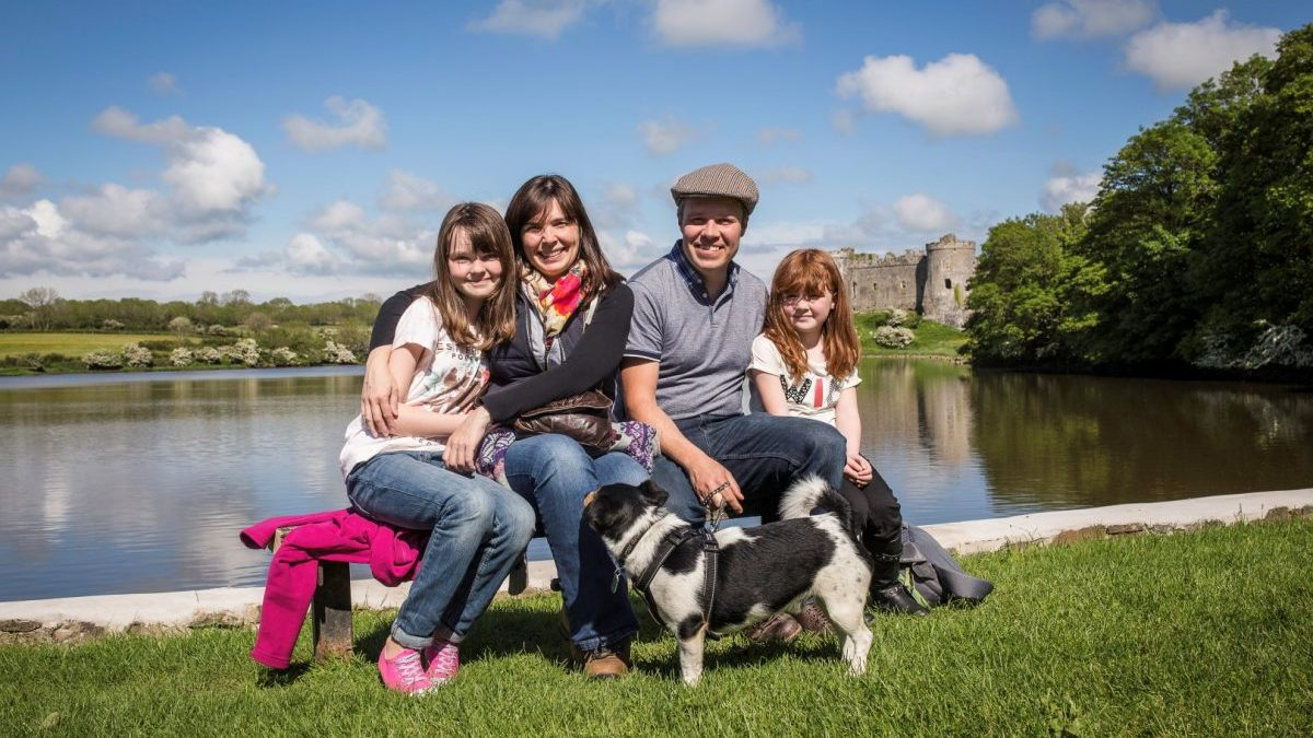 Family of four with dog sitting on Carew millpond with Carew Castle in background