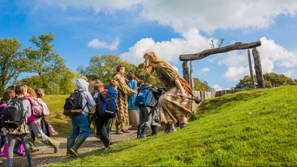 A costumed guide is running up a hill with a group of people