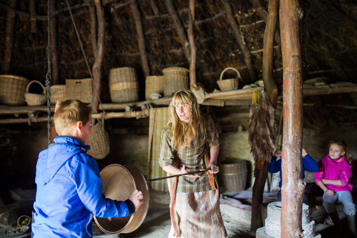A costumed guide inside a dim roundhouse at Castell Henllys Iron Age Village is speaking to a young boy with baskets on shelf in the background