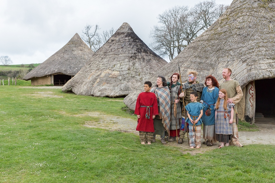 A family of seven standing outside three roundhouses at Castell Henllys
