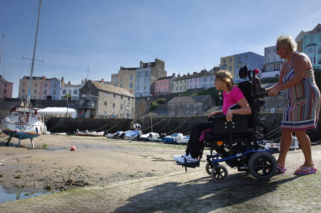 Beach wheelchair being pushed on Tenby beach