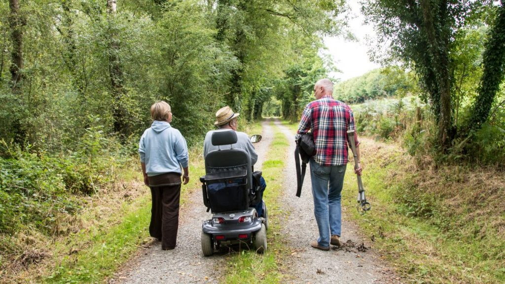 A group of 3 people including a wheelchair user on a country road