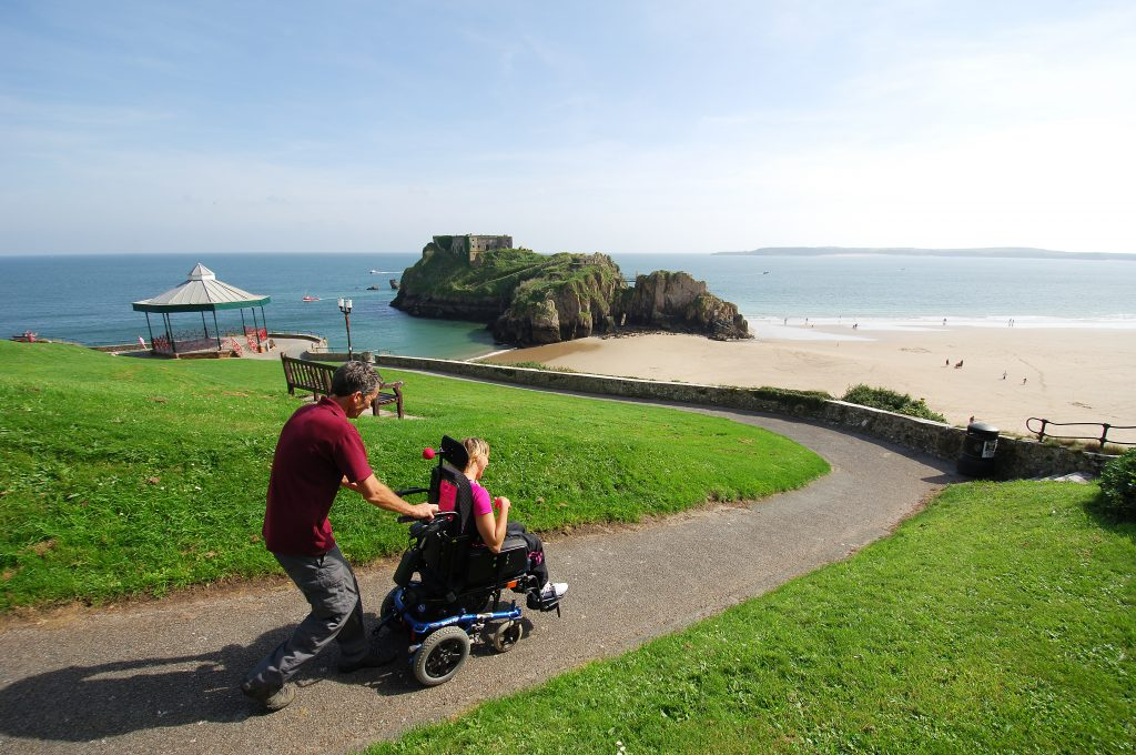 Wheelchair user being pushed on easy access path in Tenby