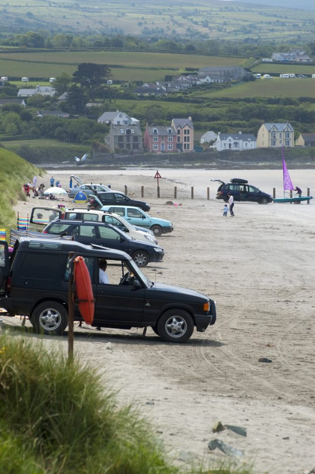 Cars parking on the beach at Newport Sands in the Pembrokeshire Coast National Park