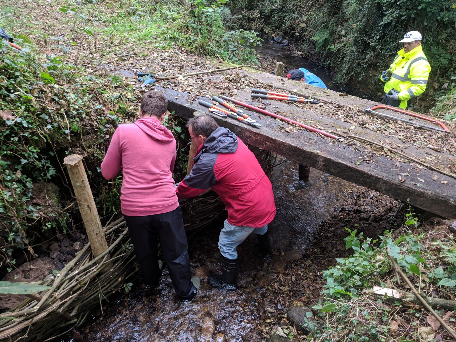 Pathways volunteers working on a bridge at Brandy Brook, Pembrokeshire Coast National Park, Wales, UK