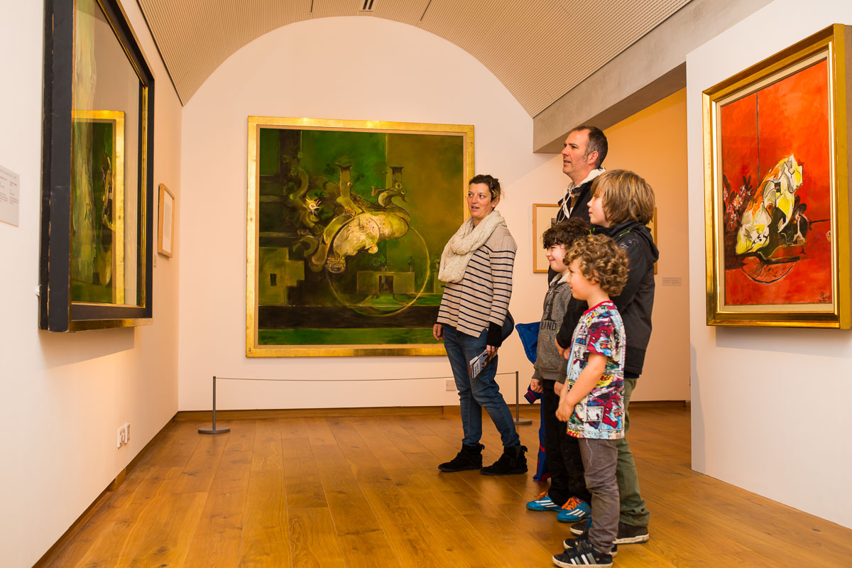 A family is viewing a Graham Sutherland painting at Oriel y Parc