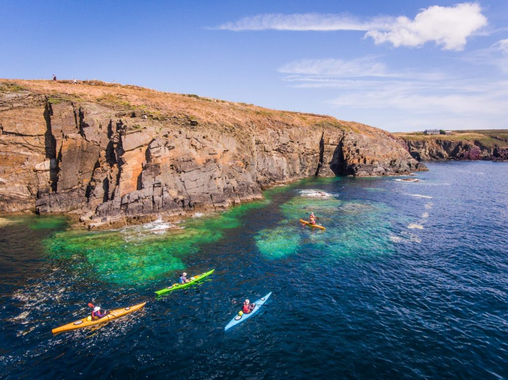 People walking on the Coast Path and kayaking at Porth Clais near St Davids, Pembrokeshire Coast National Park, Wales, UK