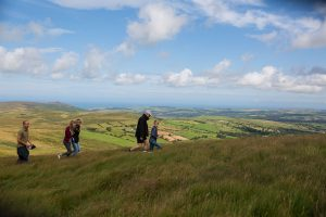 Family walking with a dog on a lead in the Preseli Hills, Pembrokeshire, Wales, UK