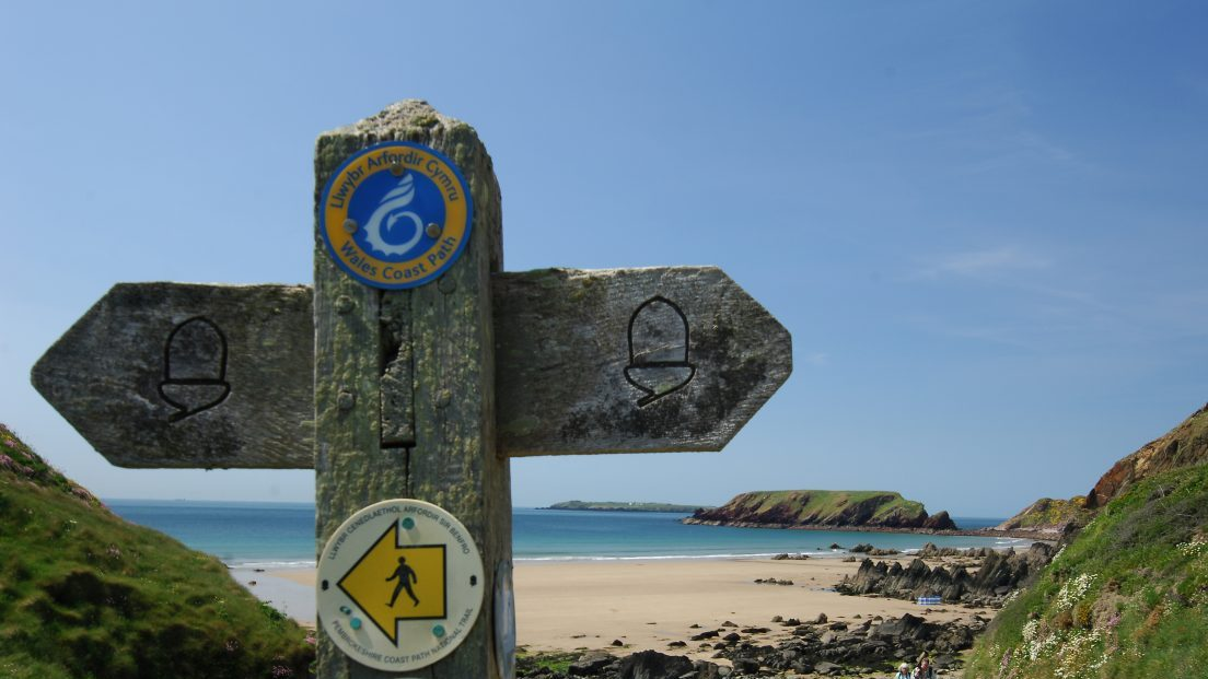 Wooden signpost on the Pembrokeshire Coast Path at Marloes Sands, Pembrokeshire, Wales, UK