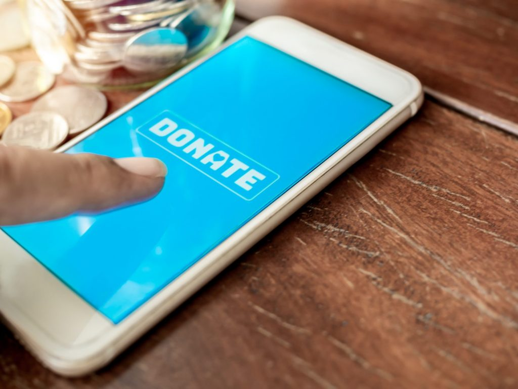 Finger pressing donate icon button on blue screen on white mobile phone with coins money on wooden background with copy space. Donation online concept.
