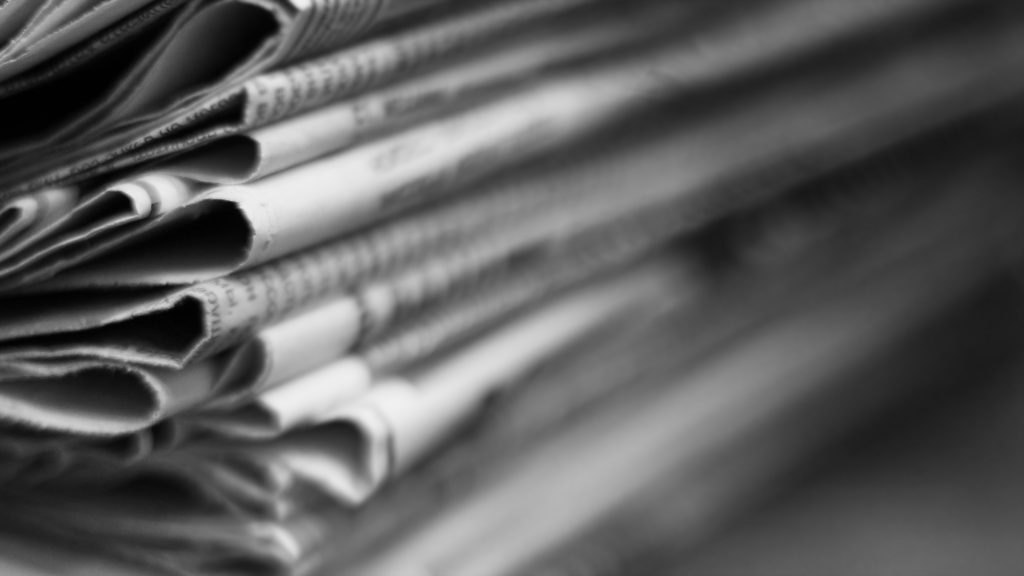 Newspapers folded and stacked in a pile. Old journals with news on wooden table. Retro style, blurred background with selective focus, close up