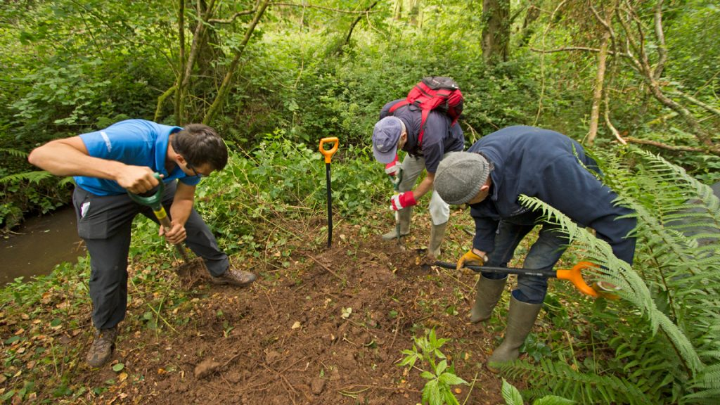 Volunteers building an otter holt with National Park Ranger Chris Taylor