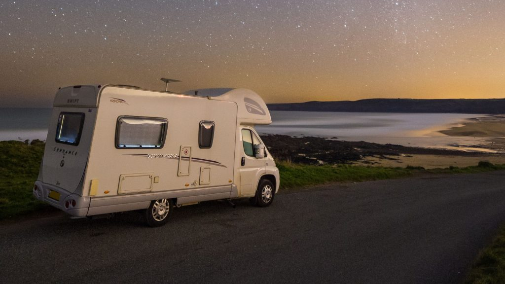 Campervan parked near coastline at dusk