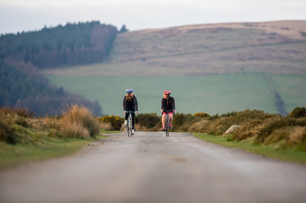 Two women cycling on a narrow road