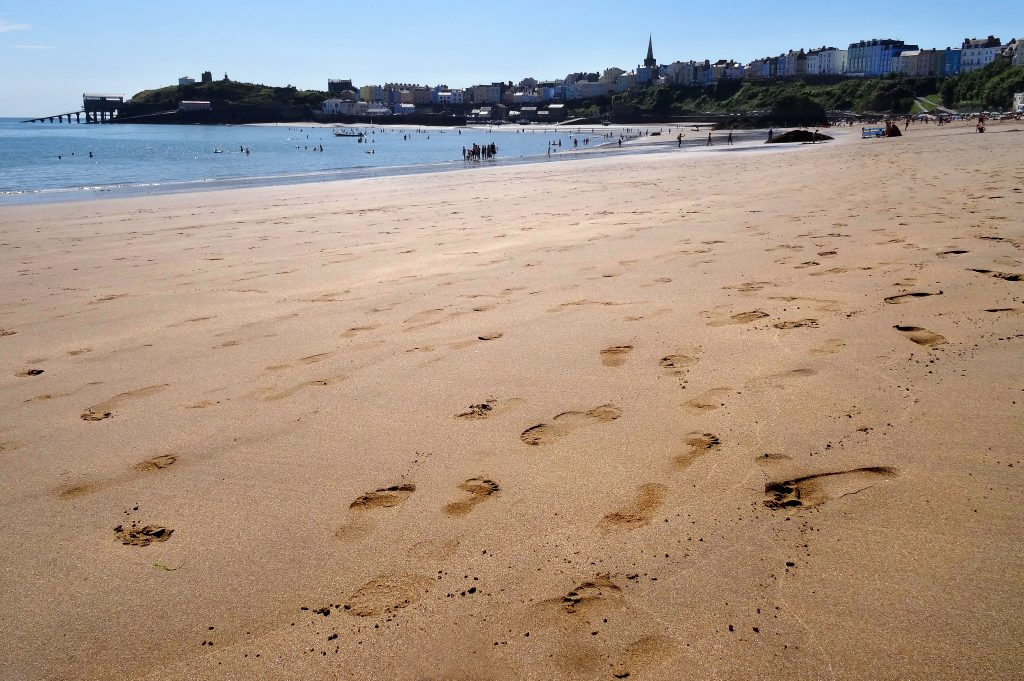 Footprints left in the sand on a beach on a sunny day with a seaside town in the background