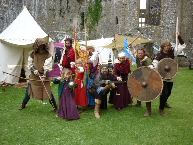 Group of people in medieval dress holding bows, swords and shields