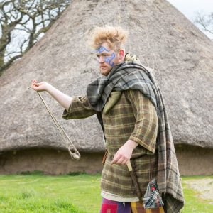 Man in iron age dress preparing to fire a sling shot