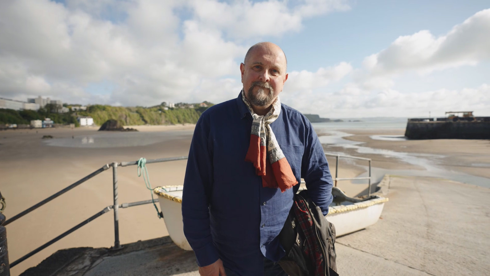 middle aged white man with goatee beard standing on a harbour wall above a sandy beach