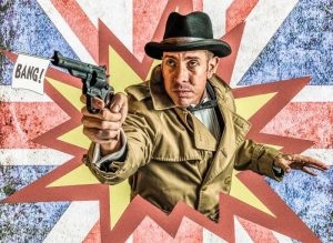 Cartoon of man dressed in 1940s attire holding a gun with the word 'bang' coming out of the barrel, bursting through of a union flag background