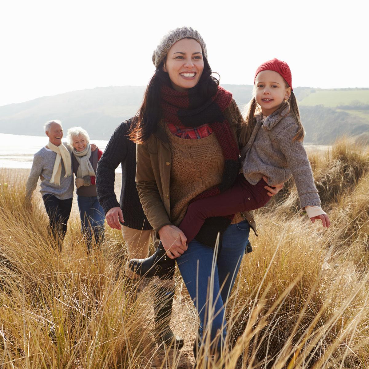 Multi generational family walking through long grassed sand dune beside beach