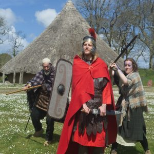 People in Roman costume posing in front of a celtic rooundhouse