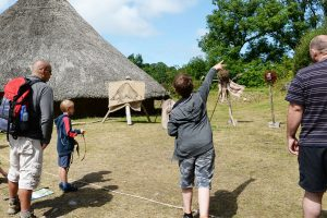 Group of people firing traditional slingshots outside a celtic roundhouse with a thatched roof