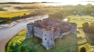 A ruined stone castle next to a river viewed from the air