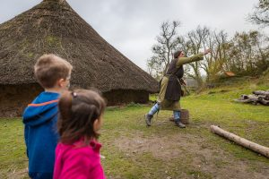 Two children watch a woman in celtic dress fire a traditional slingshot