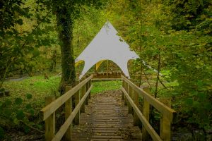 White tipi viewed from across a wooden bridge with trees and grass surround it