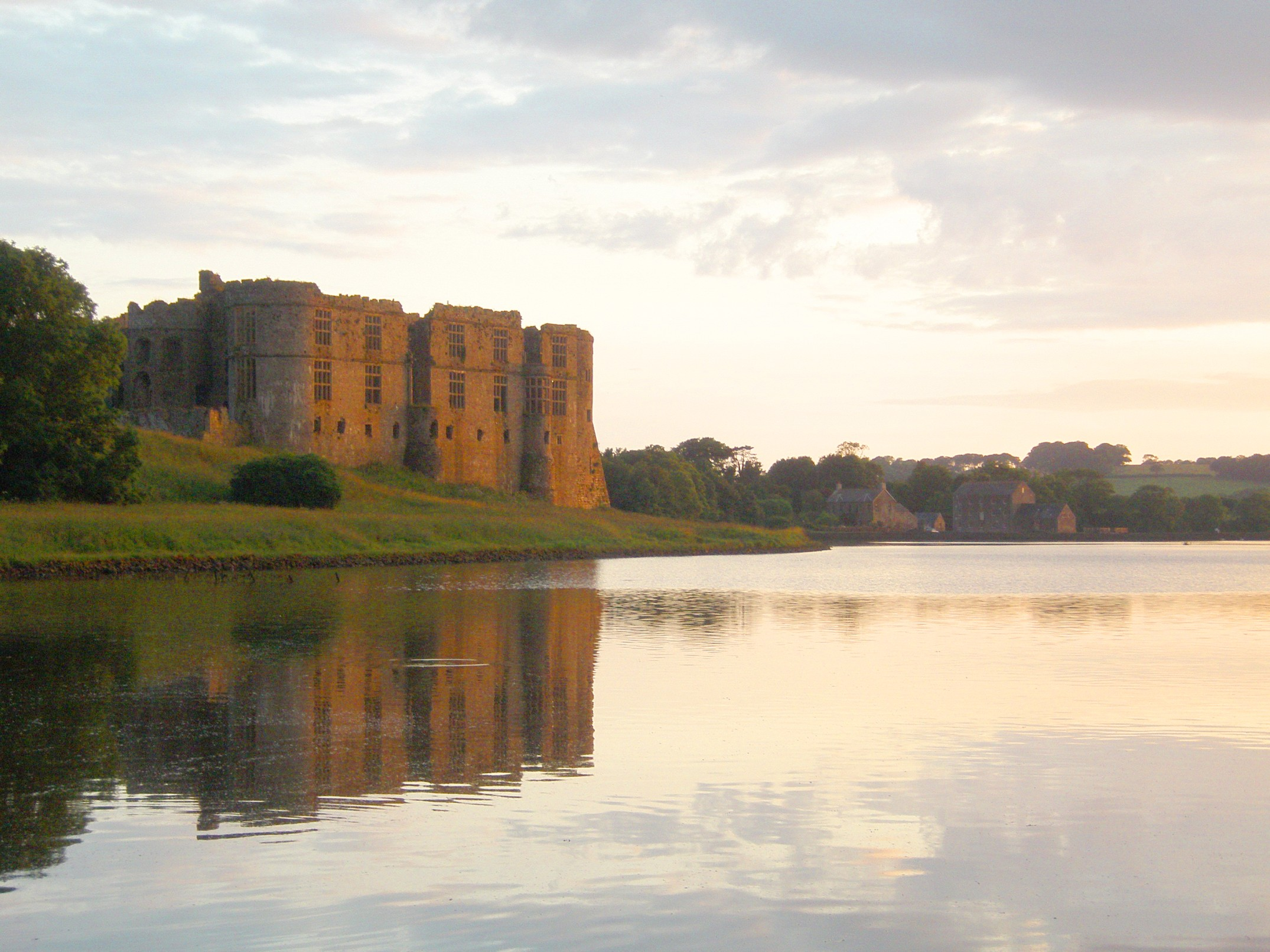 A ruined castle viewed at twilight across a calm pond