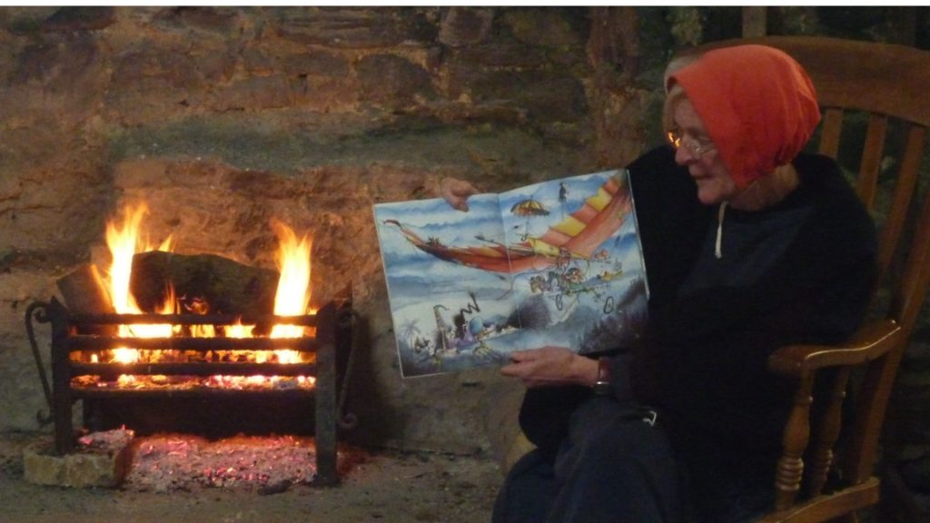 Woman sat by the fire holding a story book