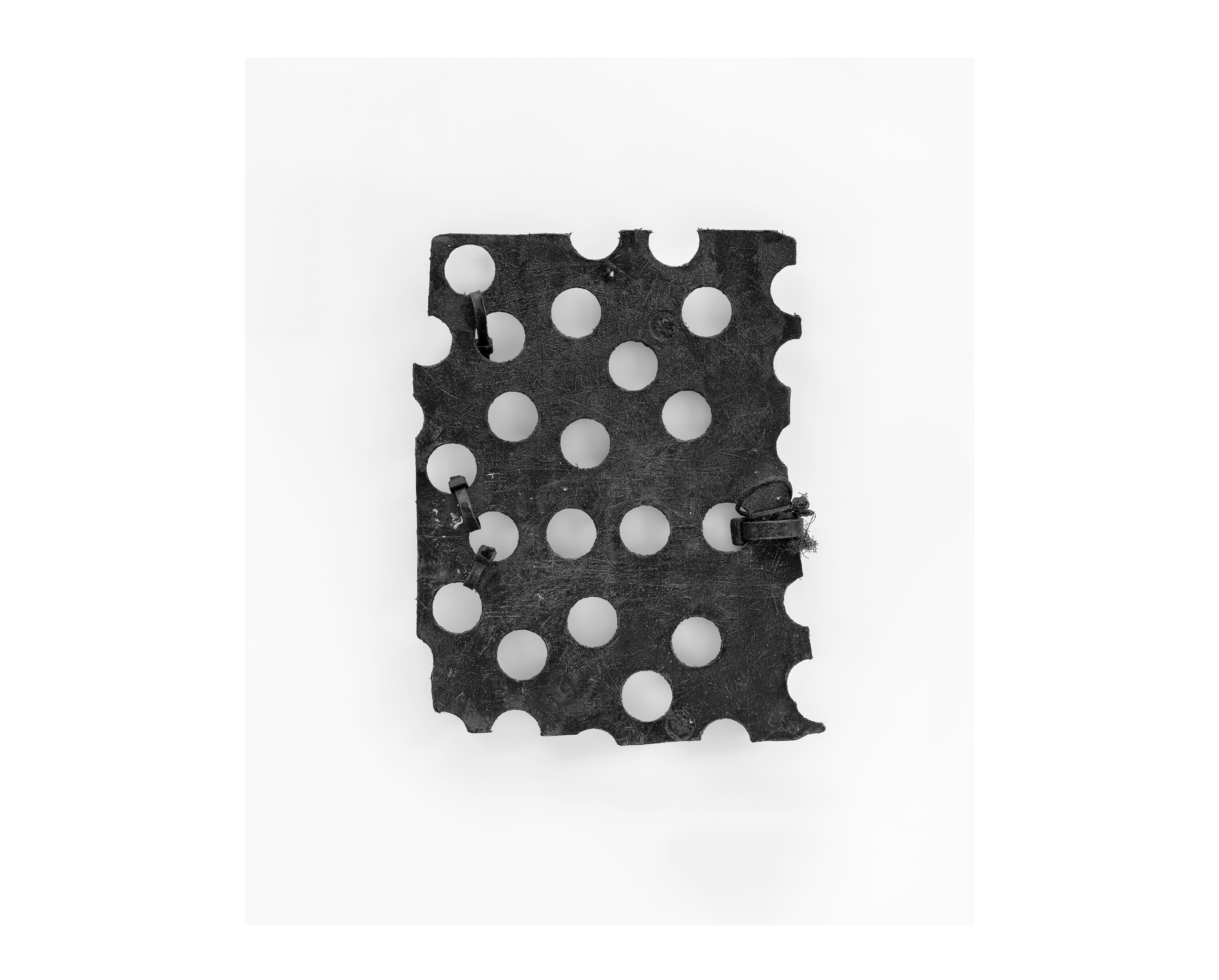 Photograph of a black piece of plastic with holes punched in it - the suspended side of a fishing 'keep box'