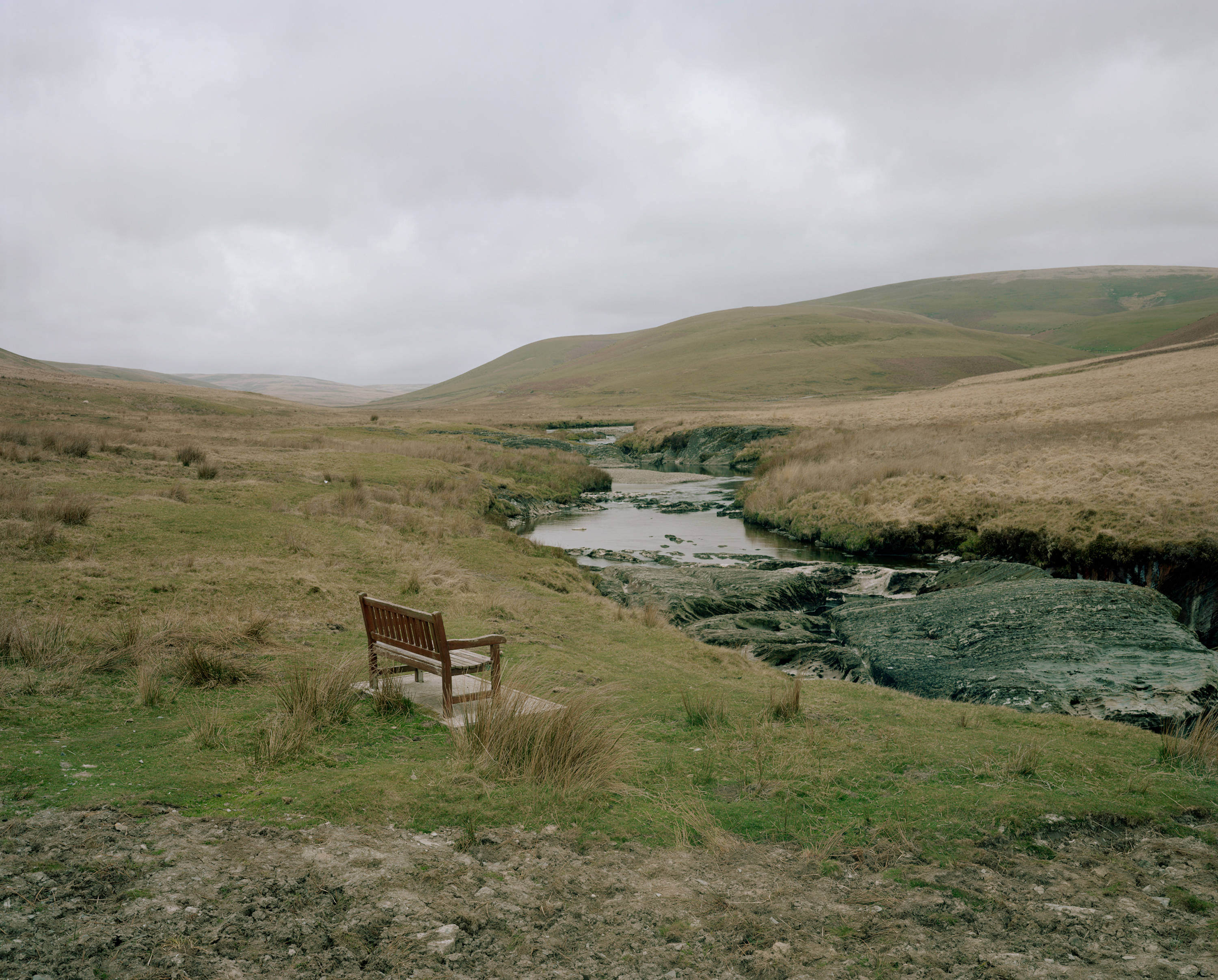 Photograph of a wooden bench in a grassy field aside a river