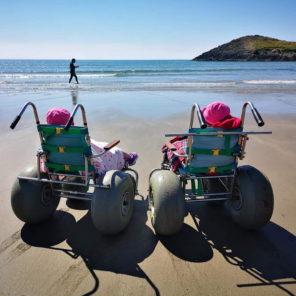 Two children on beach wheelchairs facing out to sea on a sandy beach