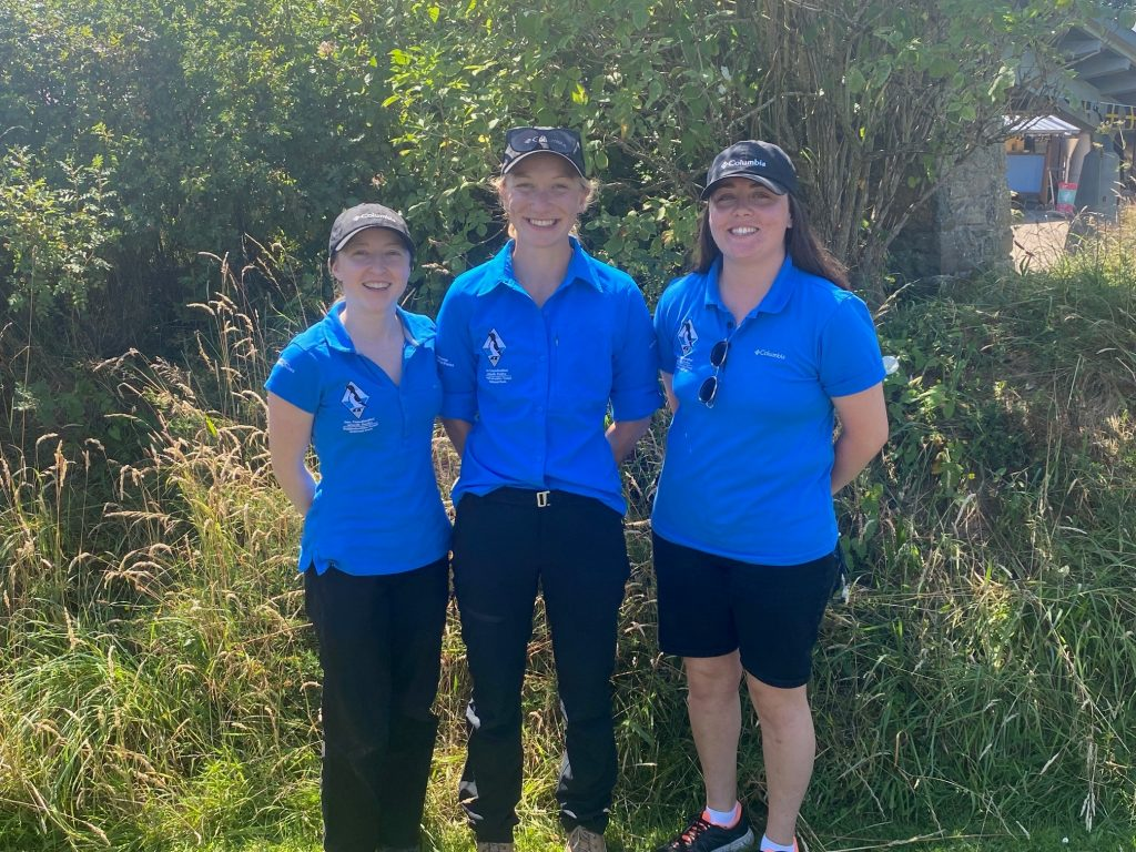Three young Pembrokeshire Coast National Park female Summer Rangers in bright blue shirts