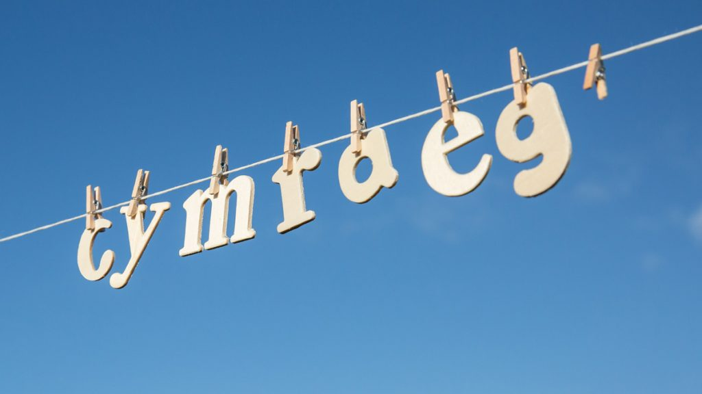 Wooden letters pegged to a washing line spelling out the word 'Cymraeg' (Welsh)