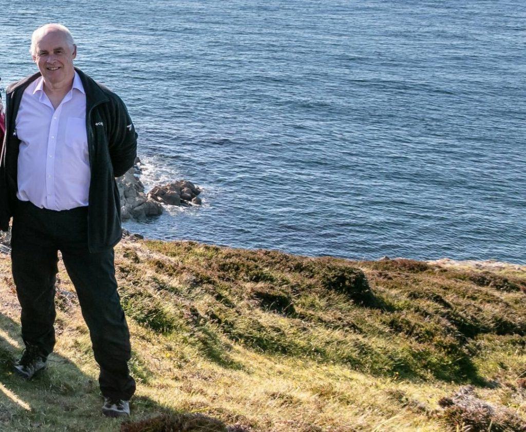 Man standing on a grassy cliff edge with a calm blue sea in the background